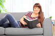 Woman lying on sofa and reading a novel at home