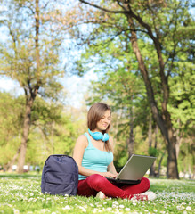 Woman studying with laptop seated on grass in park