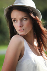 Beautiful brunette young woman outdoor with hat on