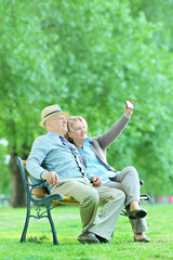 Mature couple taking selfie with cell phone in park