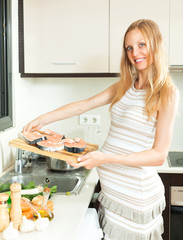 Cute pregnant blond cooks salmon in the kitchen