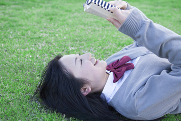 芝生で本を読む高校生