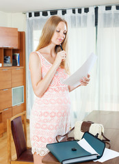 Long-haired pregnant woman looking paper document