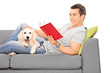 Man reading book and lying on sofa with a puppy