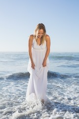 Pretty blonde standing in the sea at the beach in white sundress
