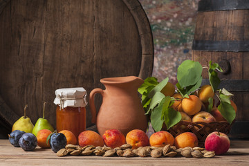 Apricot jam, fresh fruit and a wooden barrel