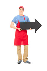 Man in apron holding a big black arrow