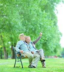 Elderly couple taking a selfie in the park