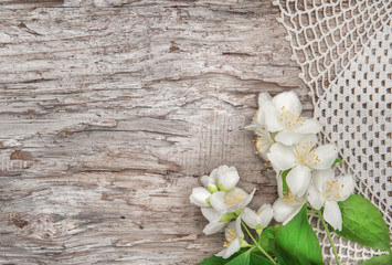 White flowers on lace fabric and old wood