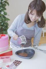 チョコレートを型に流し込む女性