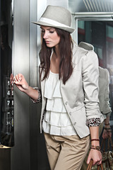 Beautiful brunette young woman with hat on using elevator