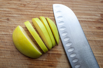 Large knife and apple on a wooden board