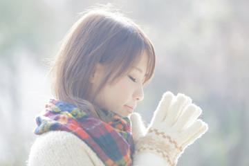 願い事をするマフラーと手袋をした女性