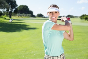 Lady golfer teeing off and smiling at camera