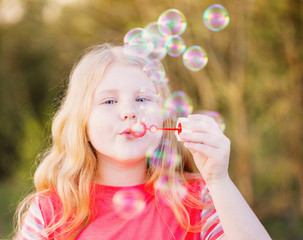 girl blowing soap bubbles outdoor at sunset