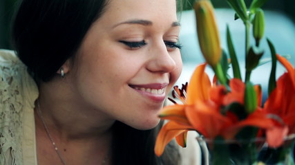Happy young woman smelling beautiful colorful flowers