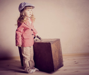 little girl with suitcase indoor