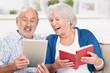 glückliches älteres paar mit tablet und buch