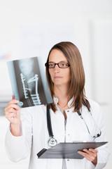 chirurgin schaut auf röntgenbild