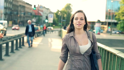 Cute young woman talking during walk in the city