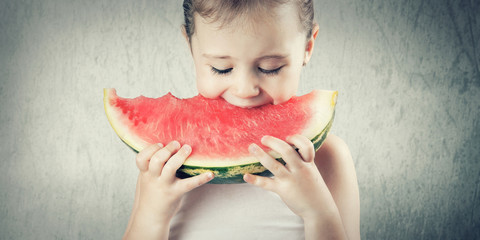 Cute little girl eating a delicious red watermelon