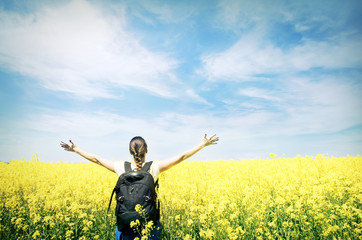 Young happy woman with backpack on a field of yellow rape