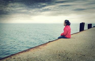 Sad little girl looks at the sea