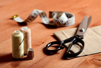 Close-up sewing tools on wooden background, vintage style