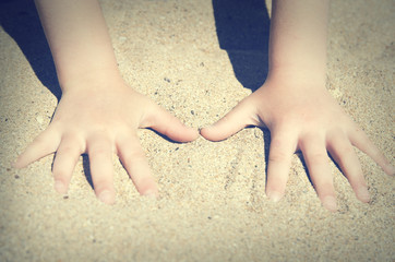 Small children's hands in the sand on the beach