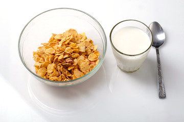 bowl of cold cereal, glass of milk and spoon on white background