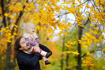 Young father and toddler girl have fun at autumn