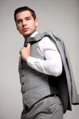 young fashion business man standing and looking away on gray