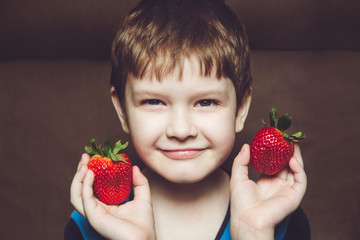 Handsome boy holds a strawberry in hands on chocolate background