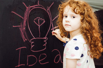 Girl writes in chalk on a blackboard. Education concept.