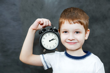 Little boy holding alarm clock.
