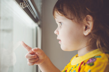 Little kid looking out the window. Toning photo.
