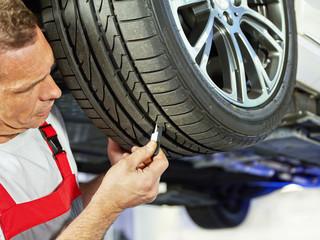 Car mechanic checks the tread pattern of a tire