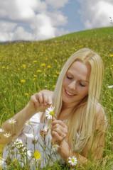 Junge Frau zupft Blütenblätter von der Blume, lächelnd, Porträt