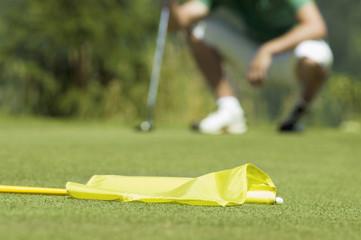 Golf-Spieler hocket auf Golfplatz