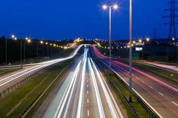 Highway traffic at the evening. Cars lights in motion. Transport