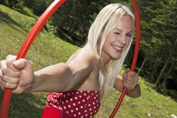 Junge Frau mit einem Hula-Hoop Reifen