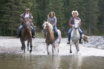 Junge Leute reiten durch Fluss, Österreich, Salzburger Land