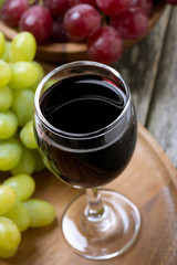 glass of red wine and grapes on a wooden board, top view