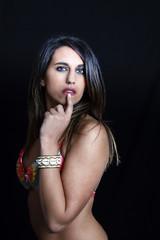 regard sexy d'une brune en studio avec le doigt sur la bouche