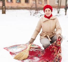 Smiling woman in cap cleans carpet with snow