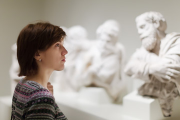 woman looking ancient sculptures