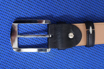 silver buckle of male black leather belt on a blue background