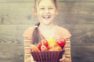girl holding vegetables