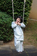 Malay girl in traditional costume on a swing