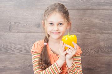little girl holding a fresh sweet vegetable on wooden background